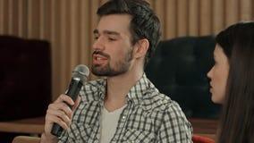 Homem novo que canta a música favorita no karaoke Fotos de Stock Royalty Free