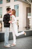 Homem novo que cede uma flor à mulher Fotos de Stock Royalty Free