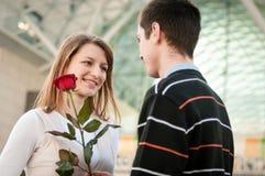 Homem novo que cede uma flor à mulher Imagem de Stock Royalty Free