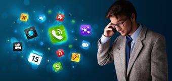 Homem novo que chama pelo telefone com vários ícones Fotografia de Stock Royalty Free