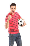 Homem novo que cheering e que prende um futebol Fotos de Stock Royalty Free