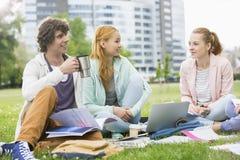 Homem novo que come o café ao estudar com os amigos fêmeas no terreno da faculdade Foto de Stock Royalty Free