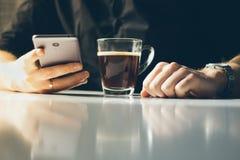 Homem novo que come o café da manhã e que lê a notícia em seu smartpho Foto de Stock Royalty Free