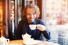 Homem novo que come o chá, inverno morno imagem de stock royalty free
