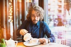 Homem novo que come o chá, inverno morno imagens de stock royalty free
