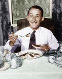 Homem novo que comem o café da manhã e sorriso (todas as pessoas descritas não são umas vivas mais longo e nenhuma propriedade ex Fotografia de Stock