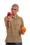 Homem novo que compara a maçã à laranja imagem de stock royalty free