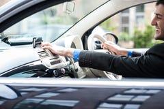 Homem novo que conduz um carro agradável, usando o dispositivo dos gps imagem de stock royalty free