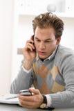 Homem novo que convida o telefone Imagem de Stock Royalty Free