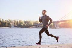 Homem novo que corre ao longo da terraplenagem do rio imagem de stock royalty free