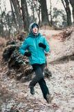 Homem novo que corre fora durante o exercício em uma floresta entre a folha Imagem de Stock