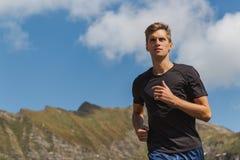 Homem novo que corre nas montanhas durante um dia ensolarado foto de stock