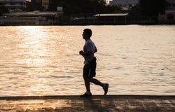 Homem novo que corre no rio fotos de stock