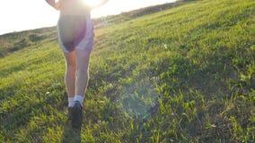 Homem novo que corre sobre o monte verde sobre o fundo do céu azul O atleta masculino está movimentando-se na natureza no por do  filme