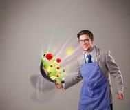 Homem novo que cozinha legumes frescos Fotografia de Stock Royalty Free
