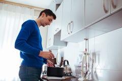 Homem novo que cozinha na cozinha em casa fotografia de stock royalty free