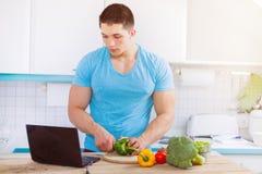 Homem novo que cozinha o eati saudável do Internet do computador dos vegetais da refeição imagem de stock royalty free