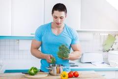 Homem novo que cozinha vegetais de preparação saudáveis da refeição no kitch imagens de stock royalty free