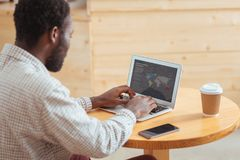 Homem novo que cria a apresentação no portátil no café Imagem de Stock Royalty Free