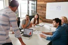 Homem novo que dá a apresentação do negócio aos colegas Fotos de Stock
