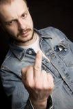 Homem novo que dá o dedo médio Foto de Stock