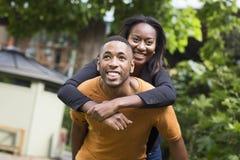 Homem novo que dá a sua amiga um reboque Fotografia de Stock Royalty Free