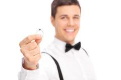 Homem novo que dá um anel de diamante a alguém Fotografia de Stock Royalty Free