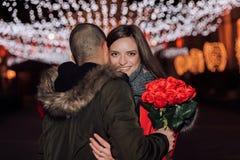 Homem novo que dá um ramalhete das rosas de sua amiga na noite imagens de stock royalty free