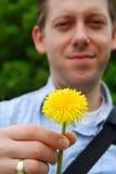 Homem novo que dá uma flor Imagens de Stock