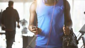 Homem novo que dança à música inspirador no smartphone no gym, estilo de vida ativo video estoque