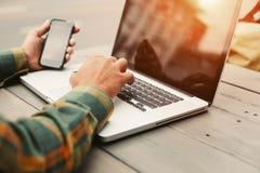 Homem novo que datilografa no computador e que senta-se no café da rua, freelancer que faz seu trabalho fora foto de stock royalty free