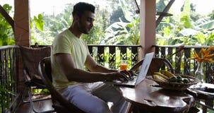 Homem novo que datilografa no laptop que come o café da manhã na raça Guy Drink Juice While Working da mistura do terraço que sen vídeos de arquivo