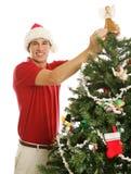 Homem novo que decora a árvore de Natal Fotografia de Stock Royalty Free