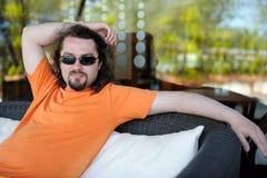 Homem novo que descansa em um recurso Fotografia de Stock