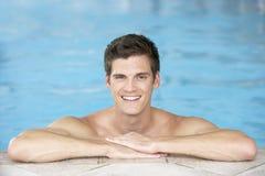 Homem novo que descansa na borda da piscina Imagens de Stock Royalty Free