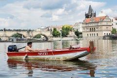 Homem novo que descansa no barco no rio Vltava perto do Charles B Imagens de Stock Royalty Free