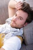 Homem novo que descansa no sofá foto de stock
