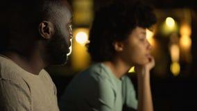 Homem novo que desculpa-se à amiga, discutindo a rua da cidade da noite dos pares, conflito video estoque
