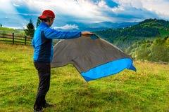 Homem novo que desdobra-se abaixo de uma cobertura de nylon impermeável para descansar na grama, em uma paisagem bonita da montan imagens de stock