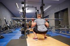 Homem novo que dobra os músculos com a barra no gym fotos de stock royalty free