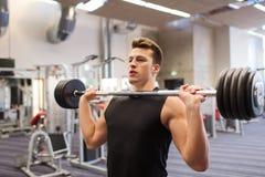 Homem novo que dobra os músculos com o barbell no gym fotografia de stock royalty free