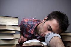 Homem novo que dorme em livros Imagens de Stock