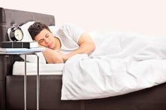 Homem novo que dorme em uma cama confortável Fotografia de Stock Royalty Free
