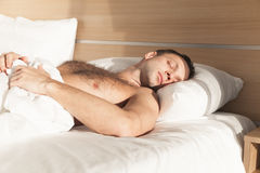 Homem novo que dorme na cama sob a cobertura branca fotografia de stock