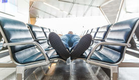 Homem novo que dorme no aeroporto Imagem de Stock