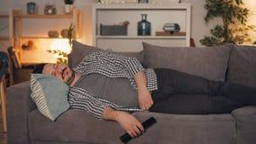 Homem novo que dorme no sofá em casa que guarda o controlo a distância para a televisão vídeos de arquivo