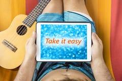 Homem novo que encontra-se em uma rede com o dispositivo da tabuleta que olha o blurr Fotos de Stock Royalty Free