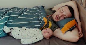 Homem novo que encontra-se na cama com bebê recém-nascido video estoque