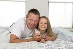 Homem novo que encontra-se na cama junto com 7 anos adoráveis do jogo velho da menina feliz em casa no li do amor do pai e da fil Fotografia de Stock