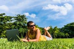 Homem novo que encontra-se na grama e que trabalha com portátil Foto de Stock Royalty Free